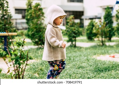 Baby girl wearing knitted cardigan walking on a playground during a strong wind. Baby, kids, baby wear, playground, weather concept