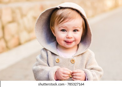 Baby girl wearing knitted cardigan coat smiling happy outdoors. Closeup portrait of happy child, toddler fashion, joy, warm urban portrait