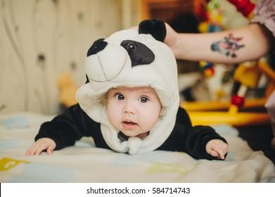 Baby girl wearing a Panda bear suit at home