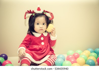 Baby girl wearing santa, happiness smiling with playing ball colorful, vintage color.