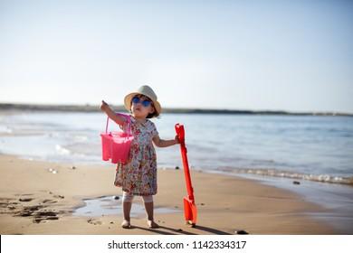baby girl wearing sunglasses running on the summer beach