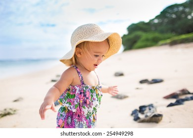 0a74afe0a89 Baby girl wearing swimsuit and hat on a tropical beach