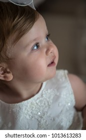 Baby girl wearing a white dress for baptism ceremony