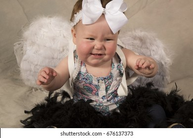 A baby girl with white feather wings with an angry face, with black feathers on her lap.