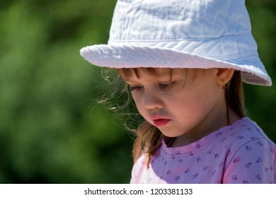 Baby girl in a white hat sadly lowered her eyes