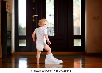 baby girl in a white T-shirt and diaper puts on a white dad's sneaker, standing in the hallway at home
