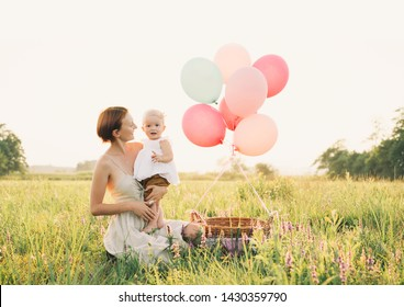 Baby girl in wicker basket with balloons in sunlight at sunset. Mother and child outdoors. First birthday. Family celebrates one year old baby on nature. Photo of healthy, dreams, vacation, holidays