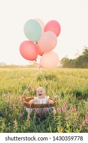 Baby girl in wicker basket with pink balloons in sunlight at summertime. Happy child on nature. First birthday party. Family celebrates one year old baby outdoors. Photo of childhood, dreams, holidays