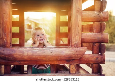 baby girl in wooden house on the playground at sunset