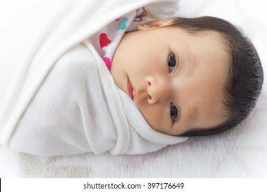 Baby girl wrapping infants in cloths in order to prevent limb movement.