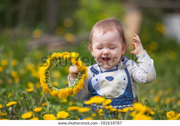 baby girl with a wreath of dandelions