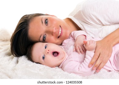 Baby girl yawning open mouth gesture with mother care near on white fur