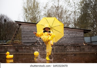 Baby girl in yellow overalls and umbrella splashes in a puddle.