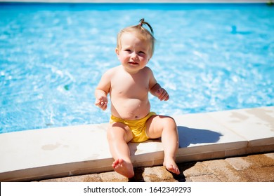 baby girl in yellow swimming diapers sitting by the pool in summer
