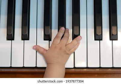 Baby Girl's Right Hand Playing with Piano Keys
