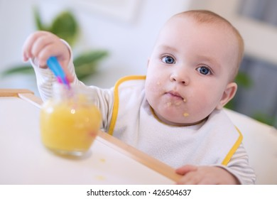A baby grabbing a jar of food while sitting in his high chair