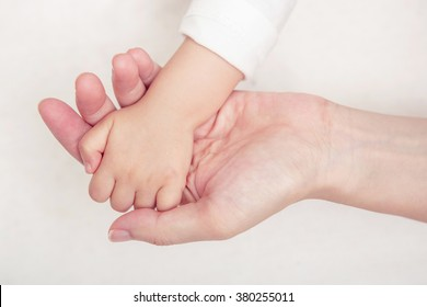Baby hand gently holding adult's finger, New family and baby protection from mom concept