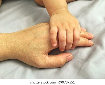 Baby hand grab old mother or grandmother hand.