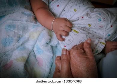 Baby hand with grandmom hand