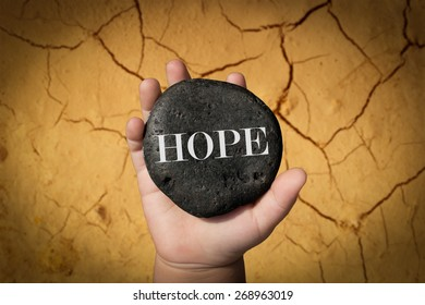 "Baby Hand Holding Up A Stone With The Word ""Hope"""
