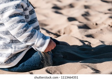 baby hand playing with sand on the beach with harsh sunlight