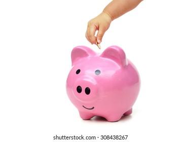baby hand putting golden coins into a pink piggy