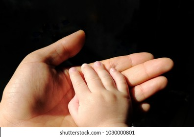 Baby hand rest over mother hand in black background