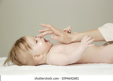 Baby handling: Woman applying moisturizing cream on her baby's face
