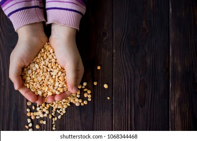 baby hands holding dried peas on wooden background