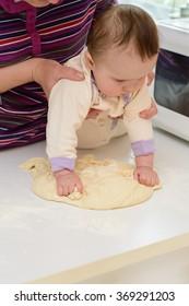 Baby hands kneads dough