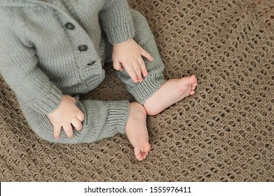 baby hands and legs and heels of a child in a gray knitted suit sitting on a brown knitted warm plaid