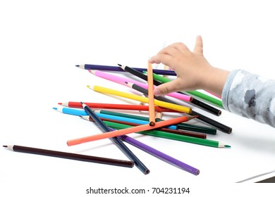 Baby hands take pencils on a white background
