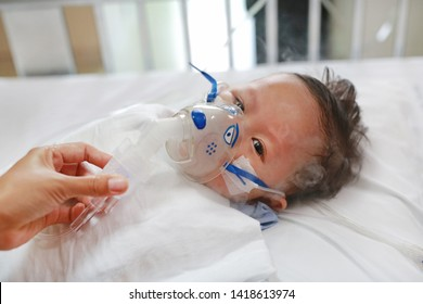 Baby has asthma and need nebulizations, Sick boy inhalation therapy by the mask of inhaler. Baby boy has a nasal congestion. Baby boy making inhalation with nebulizer.