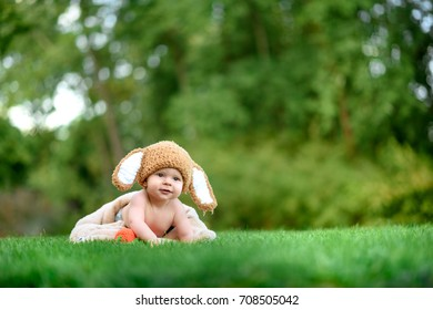 Baby in the hat like a bunny with carrot toy on green grass outdoors