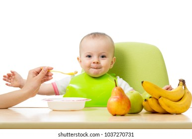 Baby having a table full of healthy food. Cheerful toddler with fruits apples, bananas, pear. Mother feeding kid fruit puree. Isolated on white background.
