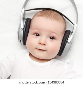 baby with headphone lies on back