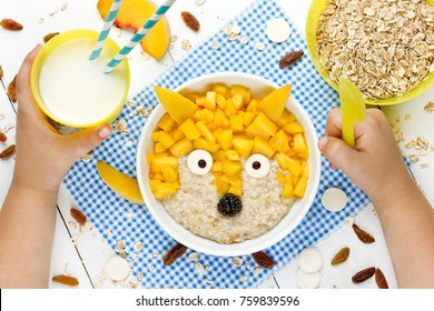 Baby healthy breakfast - sweet milk oatmeal porridge with peach shaped fox. Fun food idea for kids