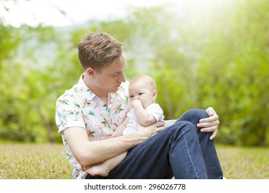 Baby with his father sitting on green grass outdoors in spring park. family outside