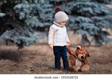 Baby and his friend bear in the park. Winnie the Pooh. Spring walk of a child with a toy. Childhood. Based on a fairy tale.