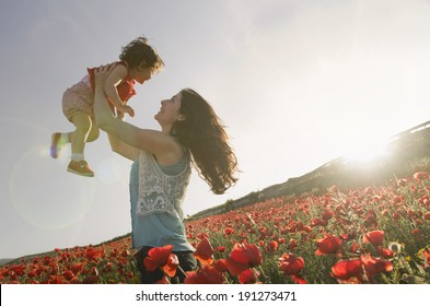 baby with his mother enjoying a field day outdoors. Sun flare in burned sky.