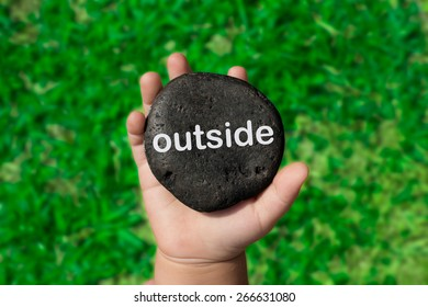 "Baby Holding Up A Black Pebble With The Word ""Outside"""