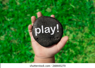 "Baby Holding Up A Black Pebble With The Word ""Play!"""