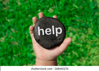 "Baby Holding Up A Black Pebble With The Word ""Help"""