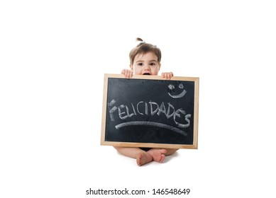 Baby holding a chalkboard with the word; felicidades hand write