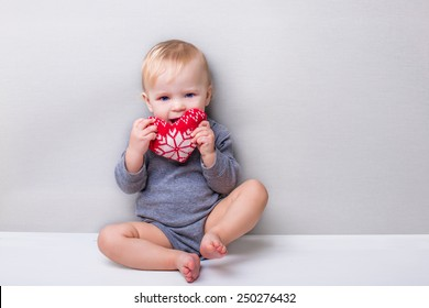 baby holding knitted toy heart christmas style in grey clothes on grey background