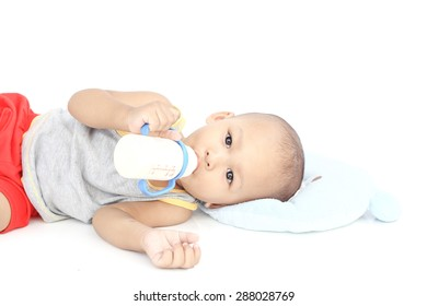 baby holding milk bottle and drinking