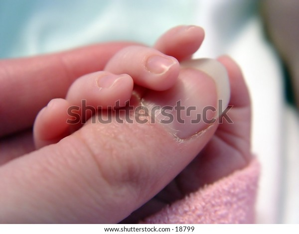 Baby holding a thumb