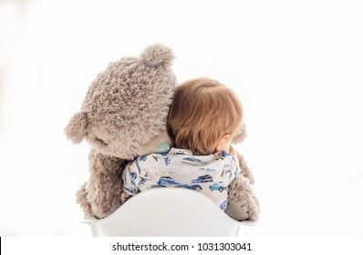 baby hugs a big teddy bear on a white background