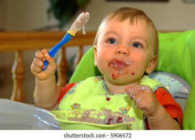 baby infant is eating by himself for the first time