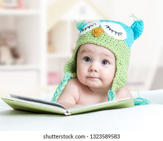 baby infant in funny owl knitted hat owl lying with opened book in nursery
